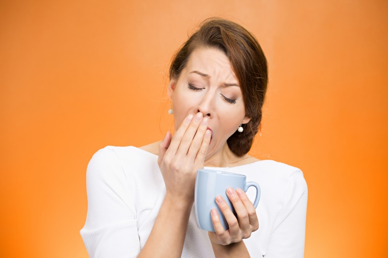 Portrait very tired falling asleep woman yawing employee holding cup coffee struggling not crash stay awake keep eyes opened isolated orange background. Human face expression, feeling emotion reaction