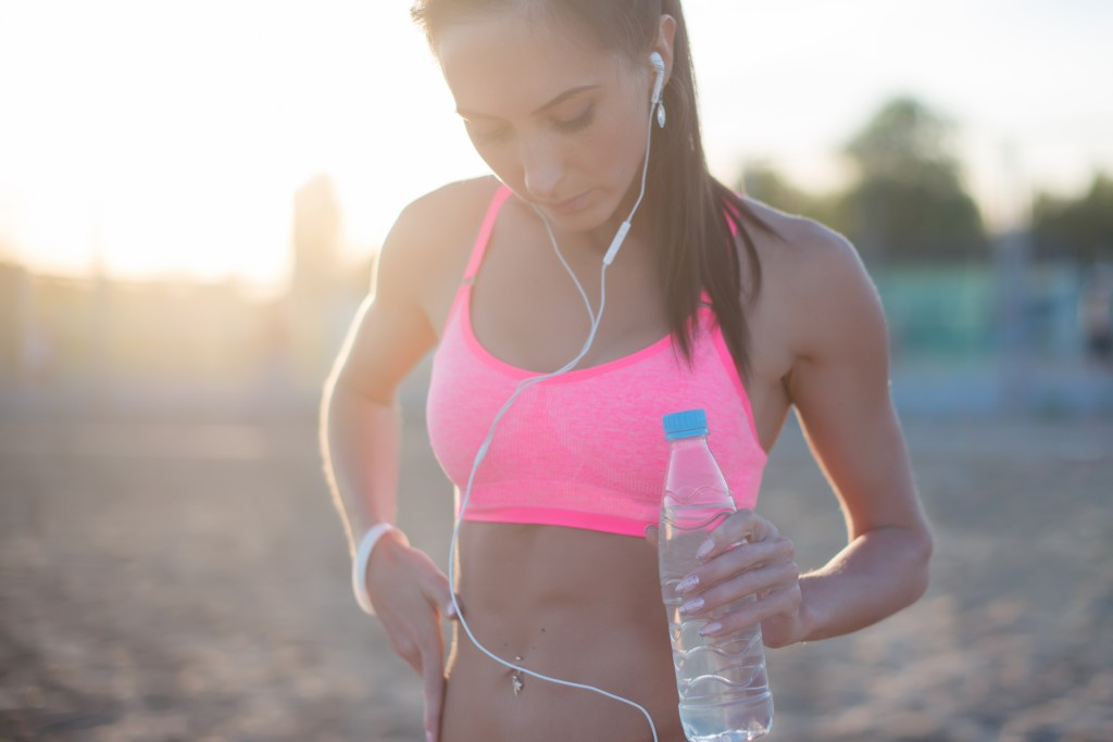 HIIT workout Beautiful fitness athlete woman resting drinking water after work out exercising on beach summer evening in sunny sunshine outdoor portrait