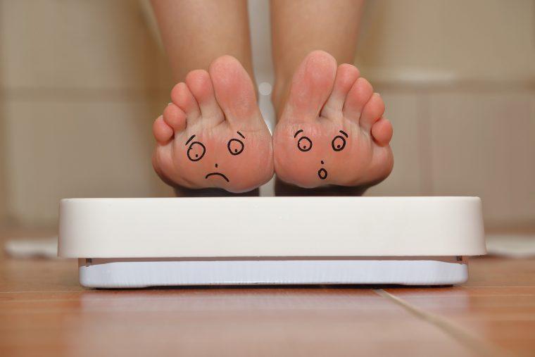 Feet on bathroom scale with hand drawn sad cute faces