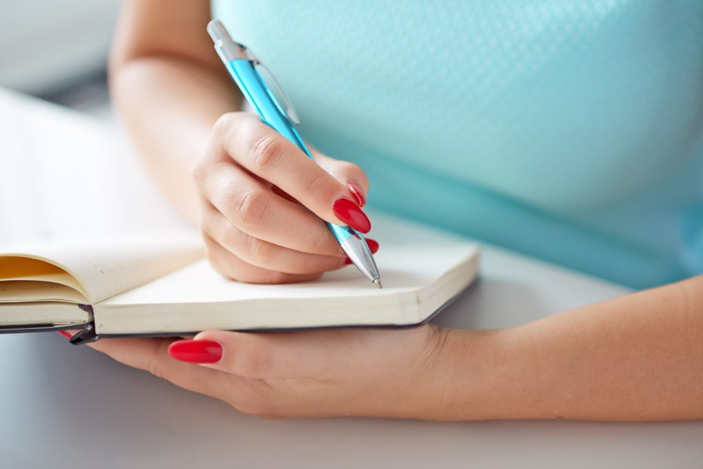 goals Young woman writes to black diary